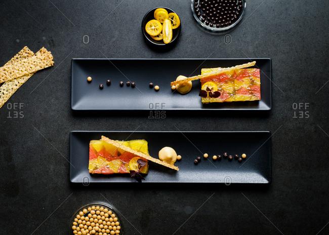 Gourmet citrus gelatin dessert on two black plates