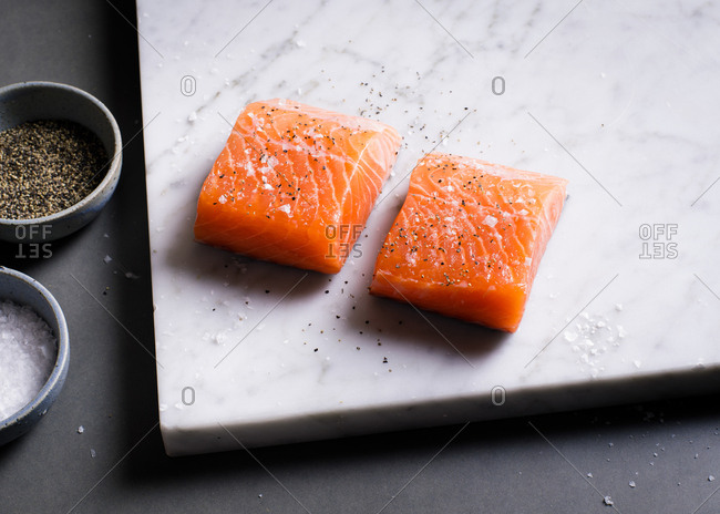 Raw salmon on white marble slab with salt and pepper