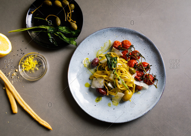 Overhead view of fresh cooked pasta with olives, capers and tomatoes