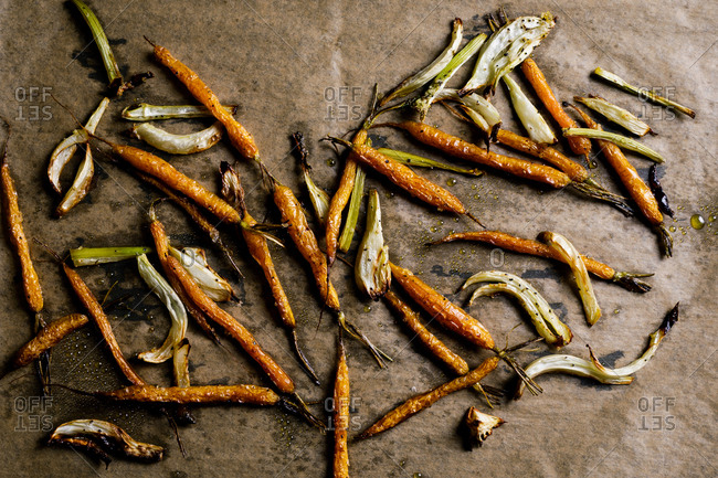 Roasted carrots and onions on gray background