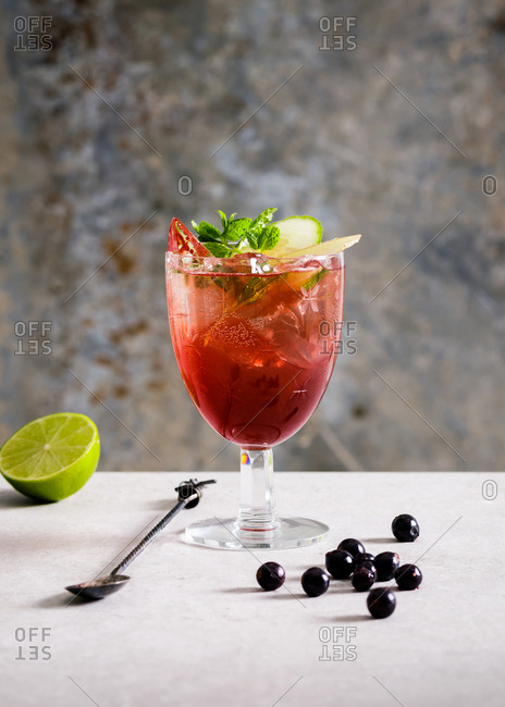 Red fruity cocktail garnished with mint and cucumber