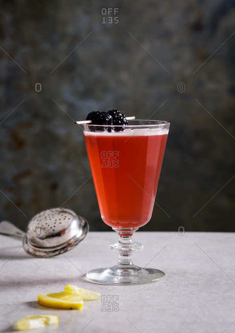 Red cocktail garnished with blackberries