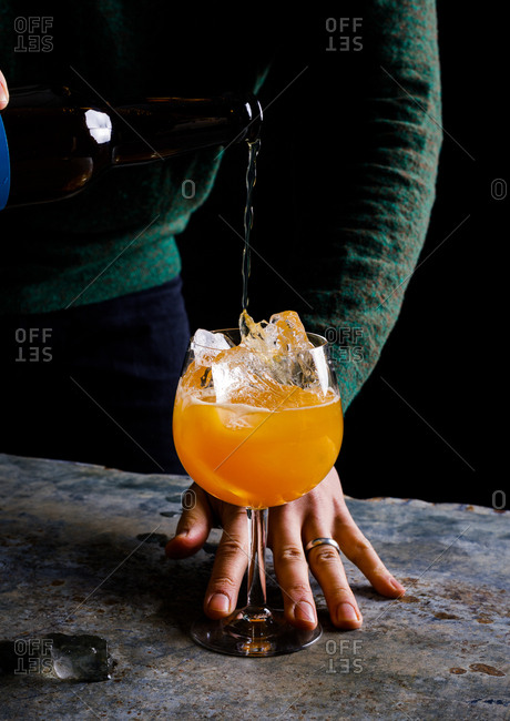 Man pouring alcohol over ice into glass