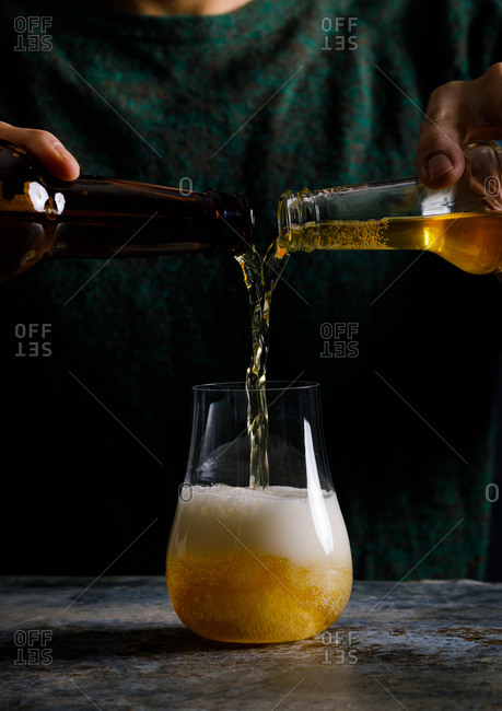Man pouring two bottles into a glass