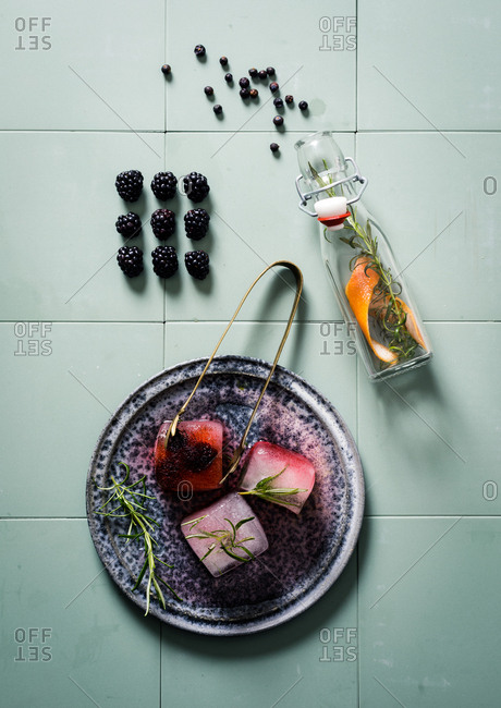 Fruit infused ice cubes on blue tile background