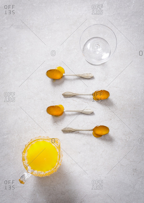 Overhead view of yellow cocktail in a pitcher and spoons filled with honey