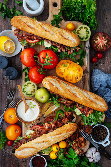 BLT subs and ingredients on a wooden cutting board