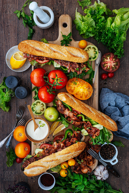 Bacon subs and ingredients on a wooden cutting board