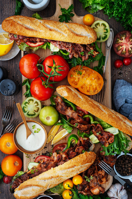 Close up of BLT subs and ingredients on a wooden cutting board