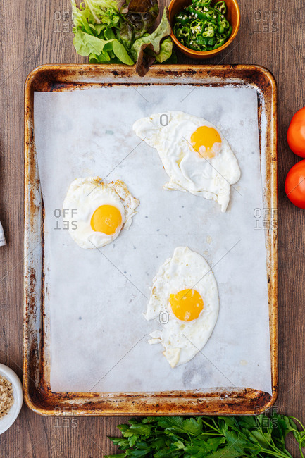 Eggs on parchment paper on a baking sheet
