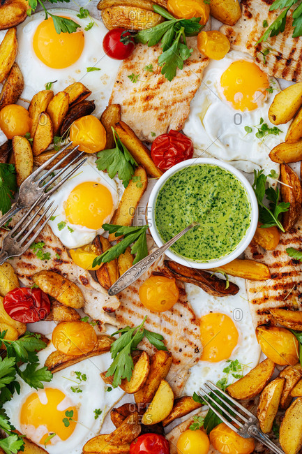 Full frame shot of eggs and potatoes with veggies and pita