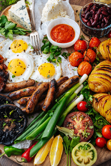 Eggs, sausage, veggies and cheese on wooden board