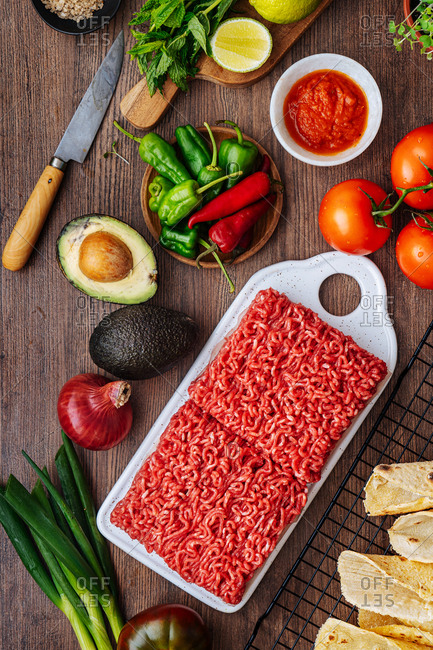 Ground beef and veggies being prepared on wooden surface