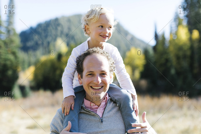 Son sitting on father's shoulders in nature