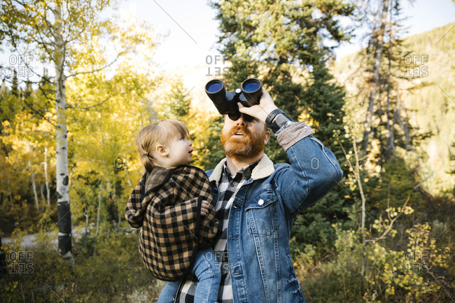 Man holding his daughter while using binoculars in forest