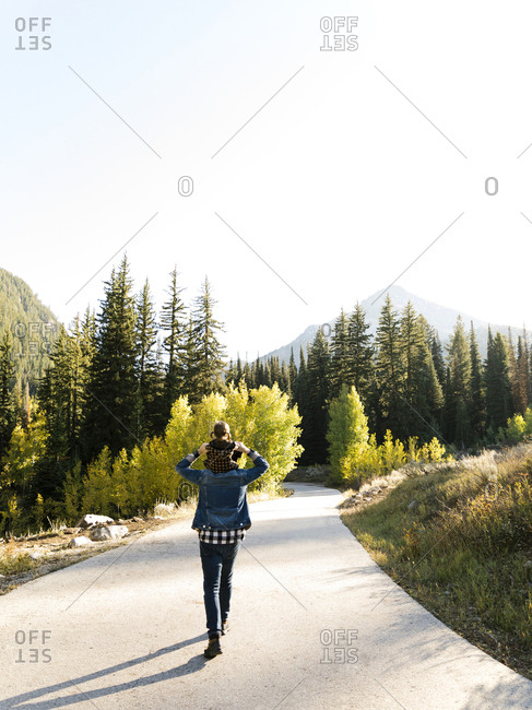 Father and daughter piggyback on road through forest