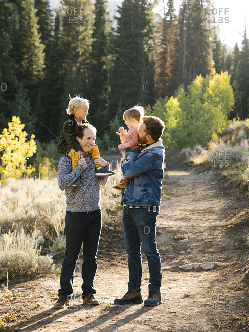 Two fathers piggybacking daughters while hiking