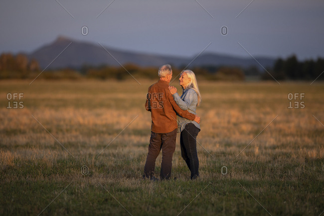 Couple in field at sunset in Picabo, Idaho, USA