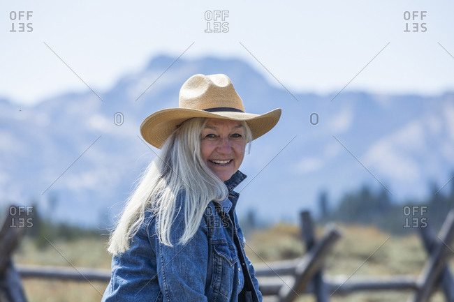 Woman wearing cowboy hat by wooden fence in Stanley, Idaho, USA