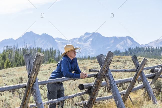Man leaning on wooden fence by mountains in Stanley, Idaho, USA