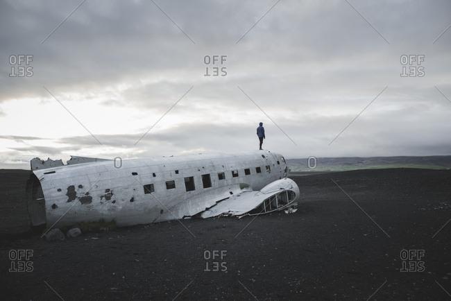 Man standing on abandoned airplane in black sand desert