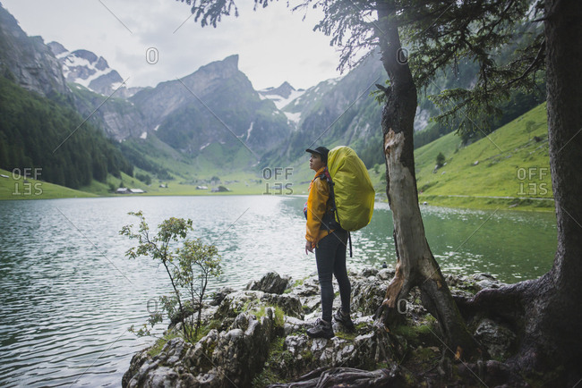 Woman wearing yellow backpack by Seealpsee lake in Appenzell Alps, Switzerland
