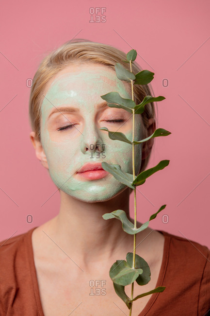 beautiful blond girl with green mask and eucalyptus branch