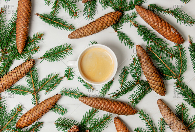 Cup of coffee with milk and Christmas fir branches and cones
