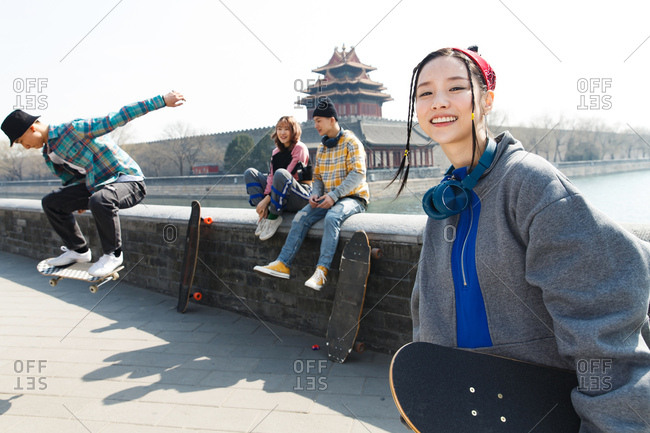 Female skater and friends hang out outdoors
