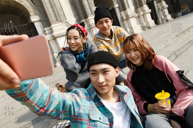 Happy young people take selfie together outdoors