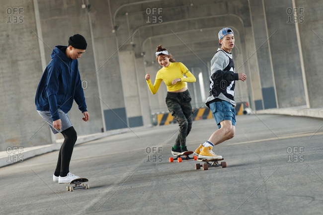 Three friends have fun skateboarding under a bridge