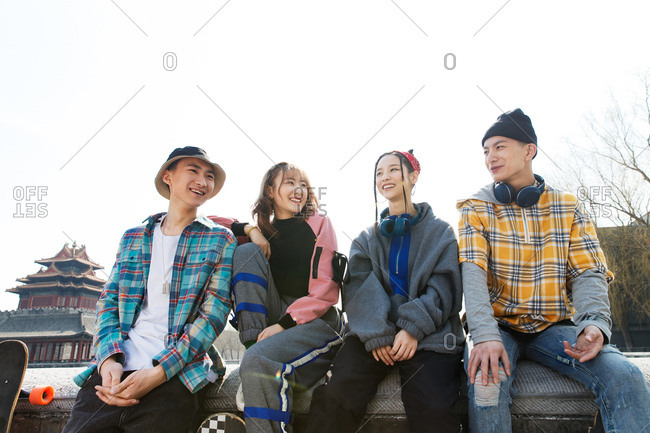 Four friends sitting together outdoors