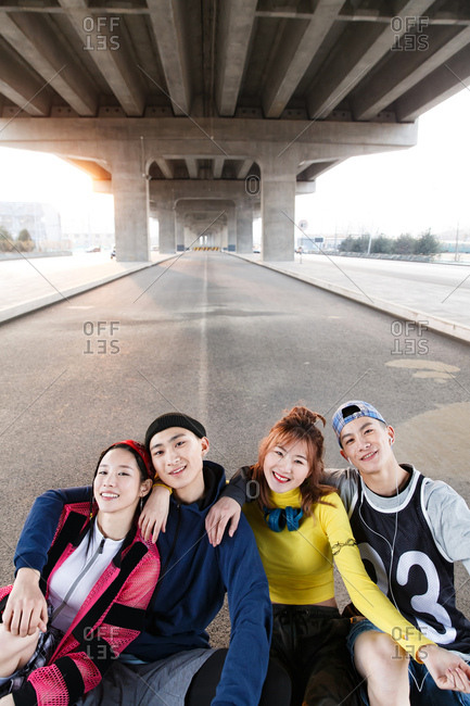 Four friends have a good time hanging out under a bridge