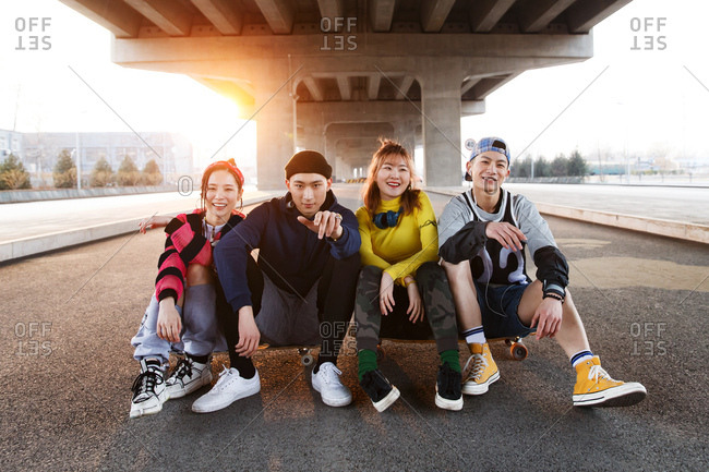Four friends sit together and hang out under a bridge