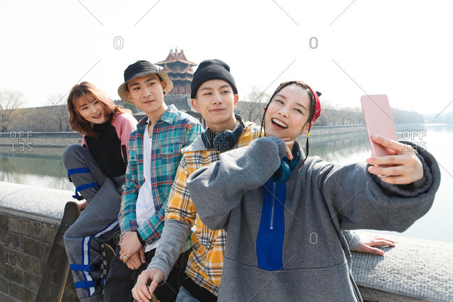 Female skater and her friends take a selfie together outdoors