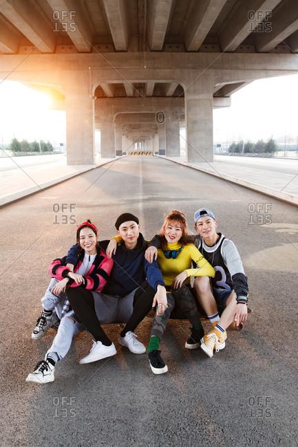 Four friends pose together under a bridge