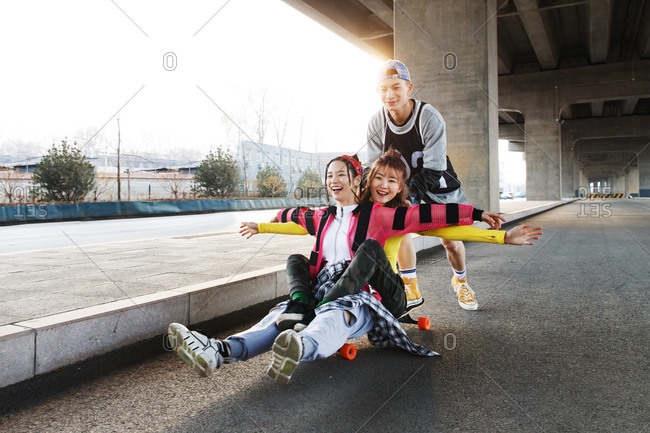 Guy pushes two girls sitting on a skateboard