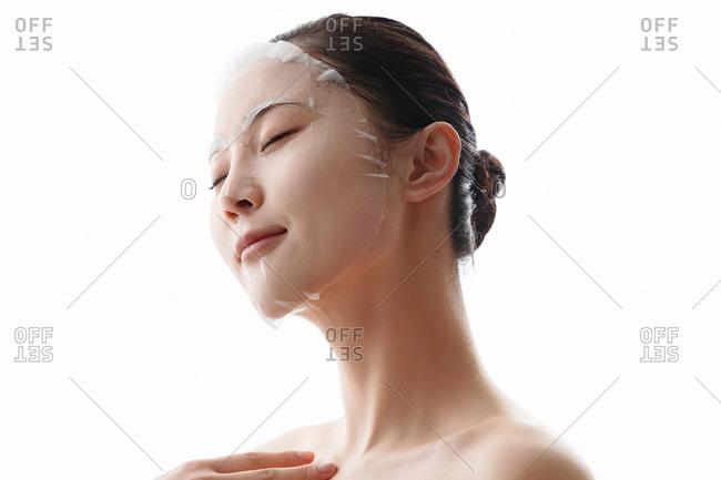 Young woman applies a facial mask