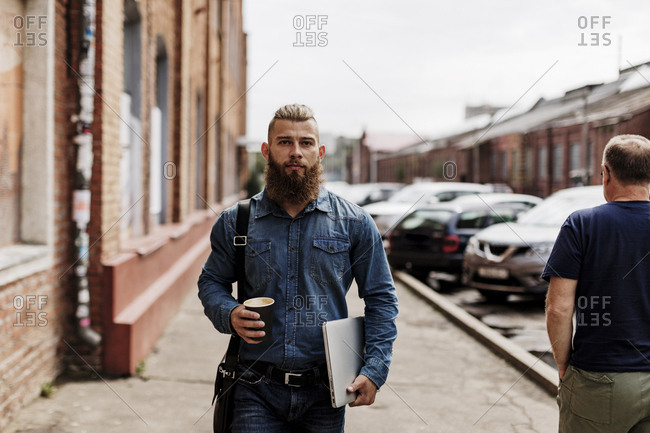 Portrait of man walking with laptop and to-go coffee