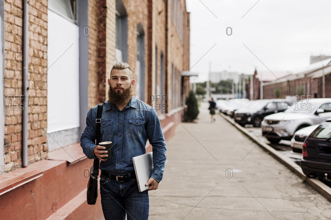 Man walking with laptop and to-go coffee