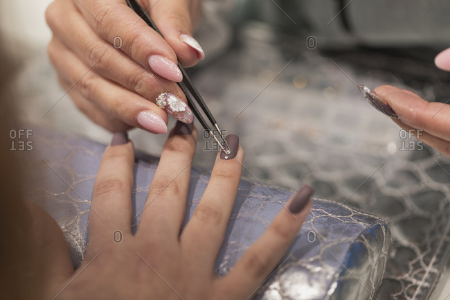Technician placing rhinestone on woman's nails during manicure
