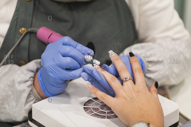 Technician using electric file on woman's nails during manicure