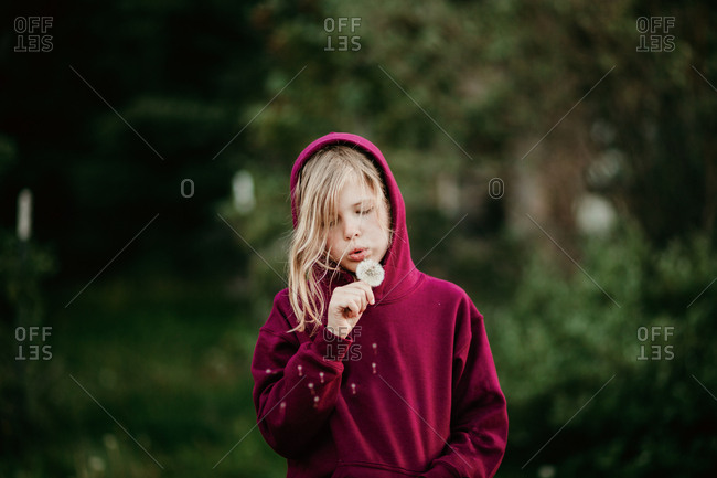 Blonde girl making a wish with a dandelion