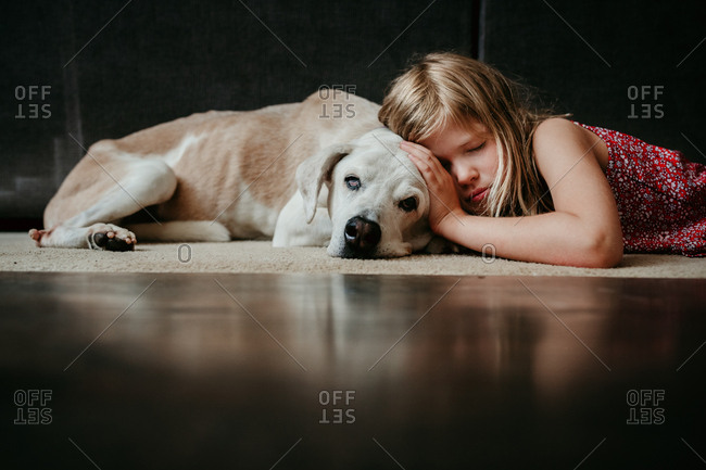 Girl laying with old dog on floor