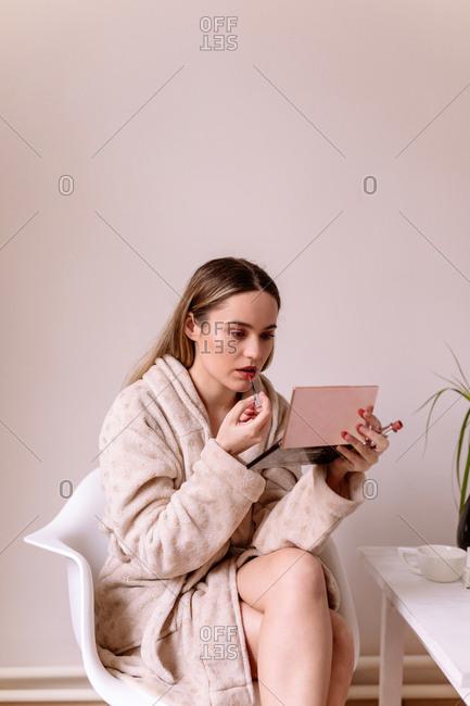 Young woman in a bathrobe applying lipstick