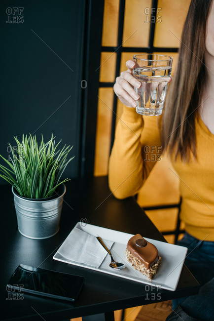 Woman holding glass of water while sitting in a coffee shop