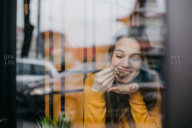 Beautiful young woman eating a chocolate cake in a coffee shop and smiling