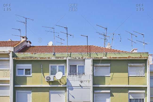 Green facade of apartment building with several antennas on top, Lisbon, Portugal