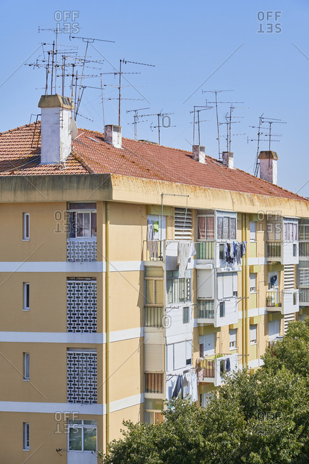 Yellow facade of apartment building with several antennas on top, Lisbon, Portugal