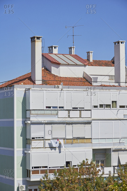 Green facade of apartment building with chimneys, Lisbon, Portugal